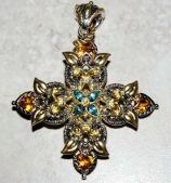 Ornate cross has a lot of gold presence and is set with citrine and blue topaz.