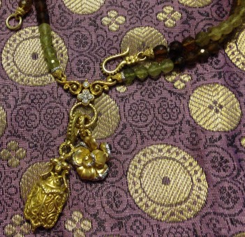 Grossular garnet necklace with gold rose and scarab charms.