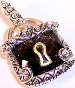 Faceted smoky quartz in silver with 18K keyhole.