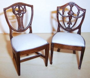 Elaborate Hepplewhite shield-back chairs by Lou Murter feature urns and garlands.