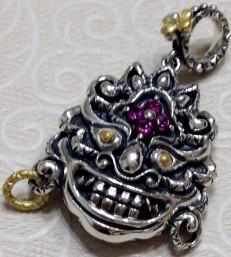 Tibetan mask charm with pink garnet.