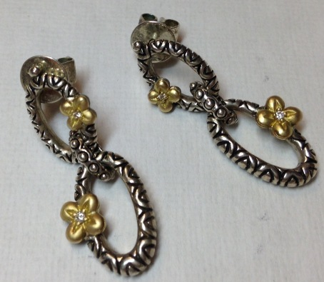 Double-link earrings with gold, diamond-centered flowers. Posts