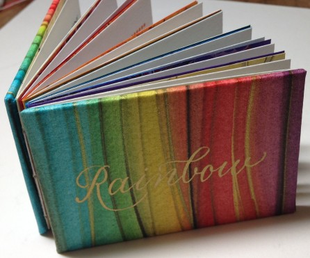 Defining the Rainbow miniature book, regular edition. Exposed spine, each section sewn with different color thread.